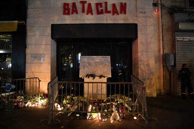 A picture taken on November 13, 2017 shows lightened candles, flowers and messages at a makeshift memorial around the commemorative plaque outside the Bataclan concert hall in tribute of the victims of the attack on the Bataclan in which 90 people were killed on November 13, 2015. France on November 13, 2017 marks two years since its worst ever terror attacks, when jihadists killed 130 people in Paris and injured hundreds of others. / AFP PHOTO / CHRISTOPHE ARCHAMBAULT